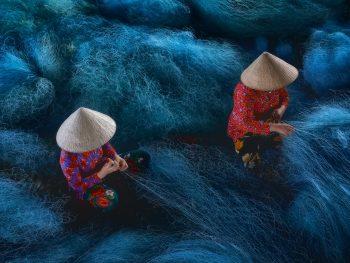 mujeres arreglando una red de pesca
